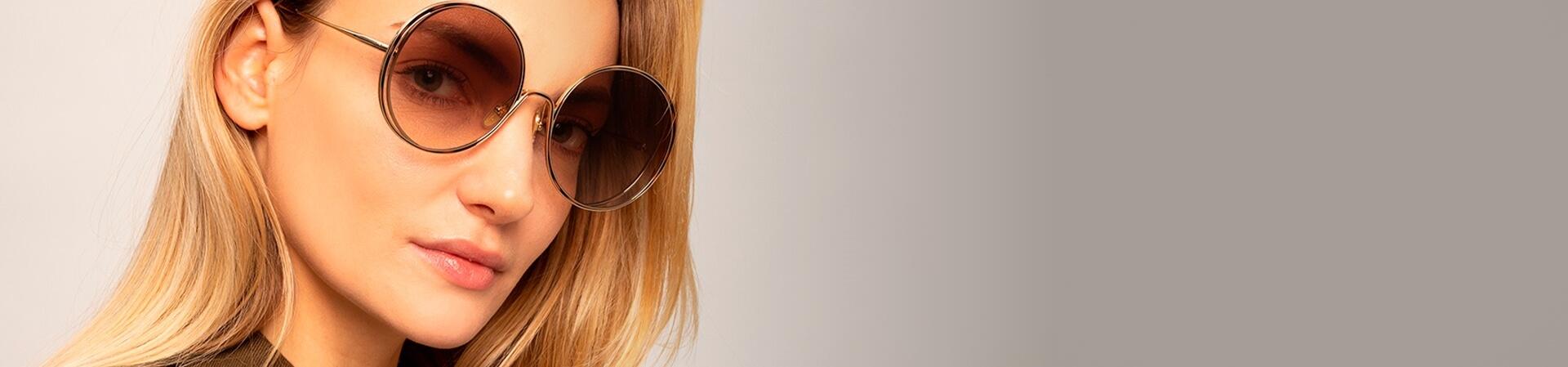 Mulher loira usando óculos de sol Chloé redondo com lentes marrons em degradê