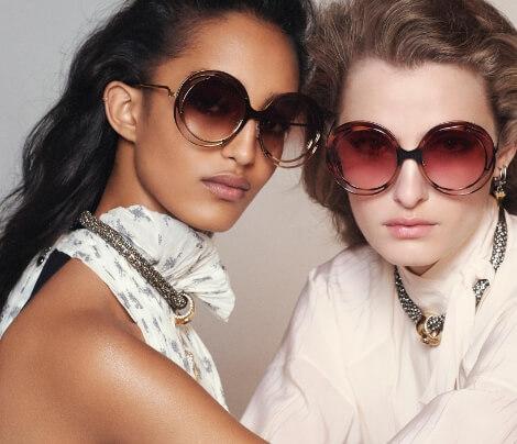 Duas mulheres, uma morena e outra loira, usando óculos Chloé de sol com armação redonda e lentes degradê em marrom e vermelho, respectivamente