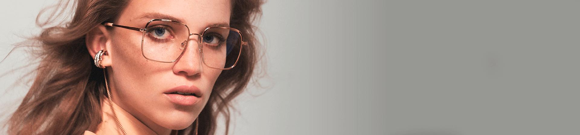 Mulher loira usando óculos de grau Chloé com armação dourada e brincos dourados