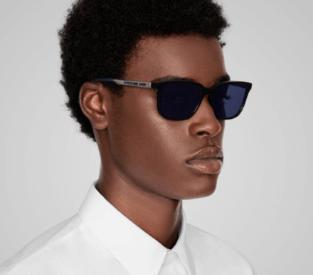 Homem negro vestindo camiseta branca, usando armação de óculos de sol Dior Homme no formato quadrado e preto