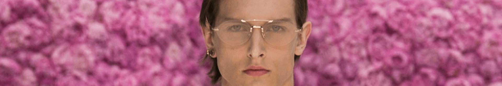Homem loiro em fundo rosa, usando Dior Homme óculos metálico no formato aviador e na cor dourada
