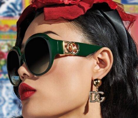 Mulher usando armação Dolce & Gabbana verde com lentes redondas escuras, batom vermelho e brinco com o logo da marca