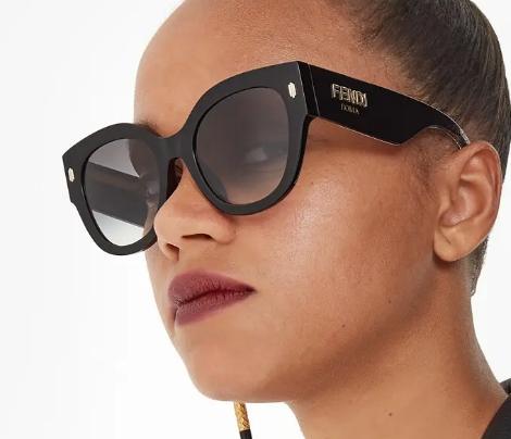 Mulher usando armação Fendi preta com lentes escuras e o logo da marca na lateral