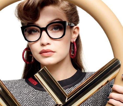 Mulher usando óculos de grau Fendi com armação gatinho em preto e lentes transparentes segurando o logo da marca