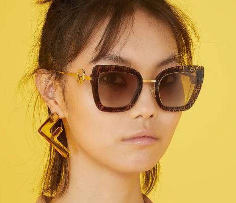 Mulher usando óculos de sol Fendi gatinho com armação marrom estampada com o logo da marca