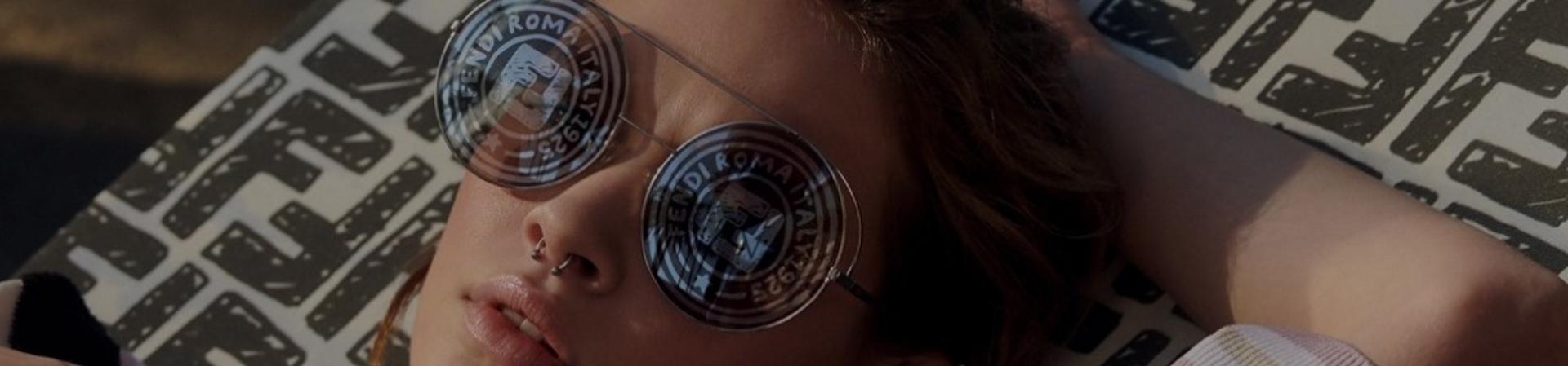 Mulher usando óculos Fendi redondo com o logo da marca estampado nas lentes