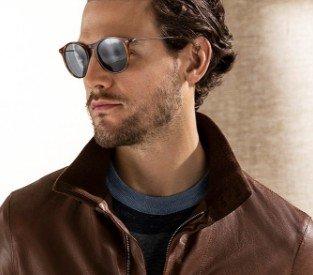 Homem com jaqueta de couro marrom, usando armação de óculos Giorgio Armani oval marrom com lentes cinzas