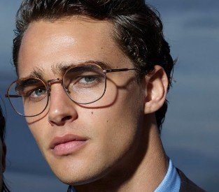 Homem usando óculos de grau Giorgio Armani no formato oval e cor prata