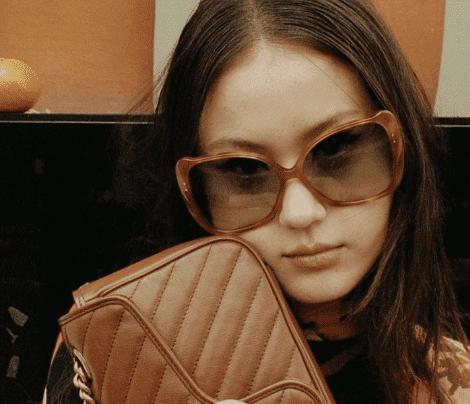 Mulher ruiva com uma bolsa marrom, usando óculos de sol Gucci feminino quadrado com lentes marrons