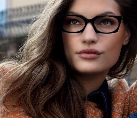 Mulher loira vestindo casaco laranja e usando armação de óculos Love Moschino quadrada na cor preta