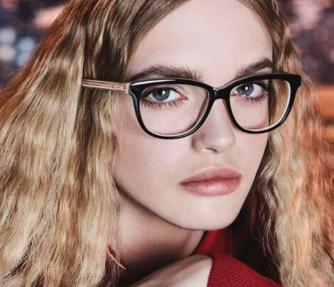 Mulher loira usando óculos de grau Love Moschino quadradp na cor preta e hastes douradas