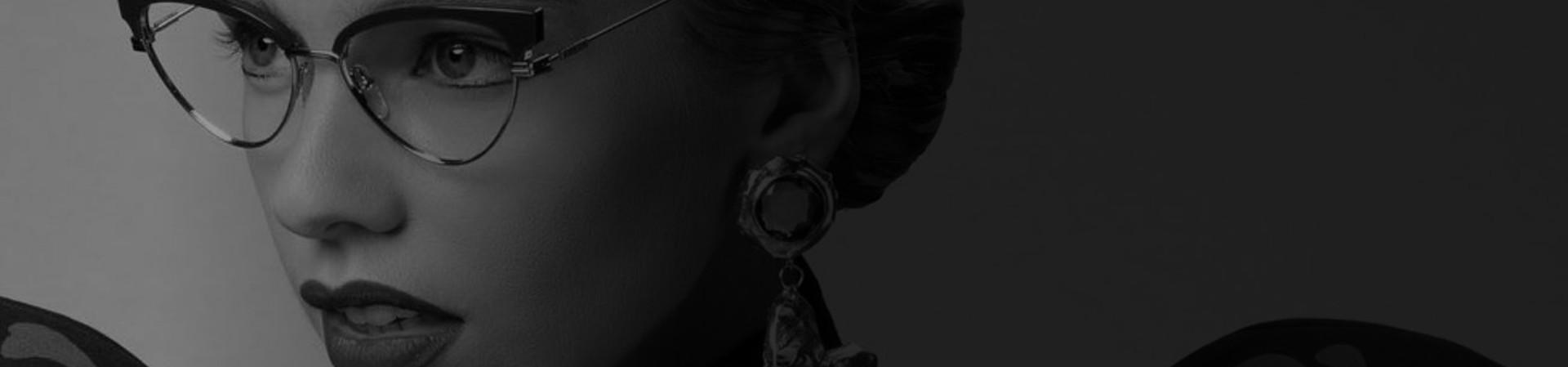 Mulher com cabelo preso e brincos de pedras, usando óculos Love Moschino em metal, no formato gatinho