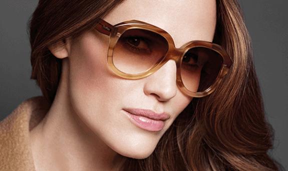 Mulher loira usando armação de óculos Max Mara marrom oval e lentes marrons em degradê