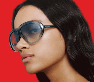 Mulher com cabelos morenos usando óculos de sol feminino Max Mara aviador cinza, com lentes cinzas em degradê