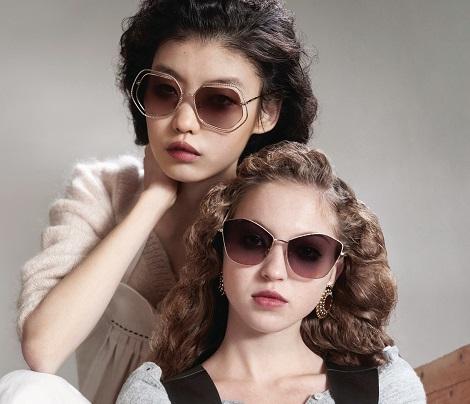 Duas mulheres usando óculos de sol Miu Miu com lentes escuras e armações angulares
