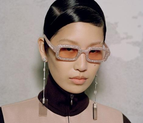 Mulher usando óculos Miu Miu retangular com lentes alaranjadas e armação brilhante