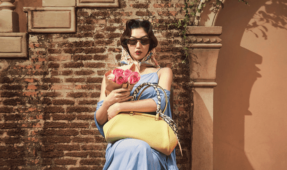 Mulher sentada usando vestido azul e armação de sol Salvatore Ferragamo marrom