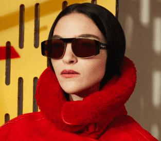 Mulher vestindo casaco vermelho e usando óculos de sol Salvetore Ferragamo preto com lentes marrons