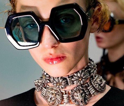 mulher usando óculos de sol gucci com colar e batom